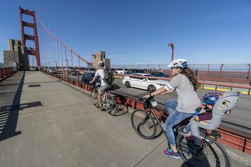 Hispanic family on bikes crossing Golden Gate Bridge.