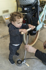 Toddler helps pump up bike tire.