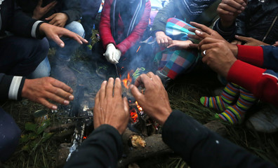 Migrants sit around a fire to warm themselves in a camp in Rigonce
