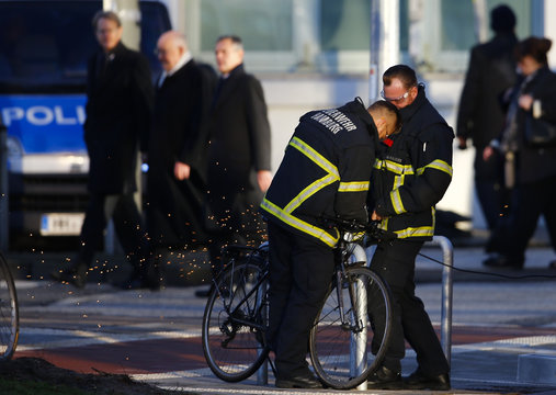 German firefighters cut off the chain locking the bicycle parked in a security area near the St. Michael's Church in Hamburg