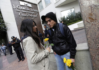 A couple hold flowers outside a funeral home after hearse that left home of Colombian Nobel Prize laureate Garcia Marquez arrived here, in Mexico City
