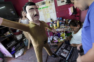 """Workers refer to images on a  laptop in front a pinata depicting drug lord Joaquin """"El Chapo"""" Guzman at a workshop in Reynosa"""