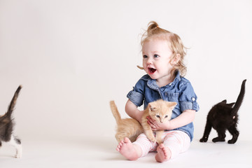 Cute toddle girl plays with baby kittens