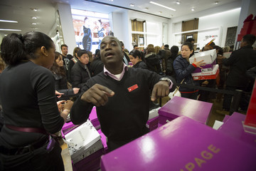 Ssales assistant stands amongst shoes in Macy's to kick off Black Friday sales in New York
