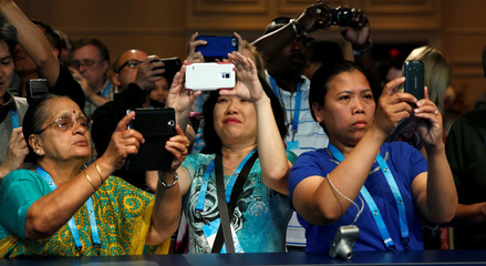 Relatives take photos as students take the stage for a preliminary round of the 89th annual Scripps National Spelling Bee at National Harbor in Maryland
