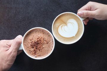 Canvas Prints Chocolate Top view image of man and woman's hands holding coffee and hot chocolate cups with wooden table background