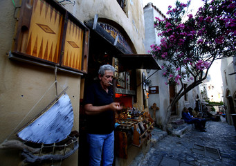 Theodoros Konstas smokes a cigarette as he stands by his shop inside the medieval castle of Monemvasia