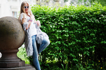 Stylish blonde woman wear at jeans, sunglasses and girl sleeveless with white shirt against bushes at street. Fashion urban model portrait.