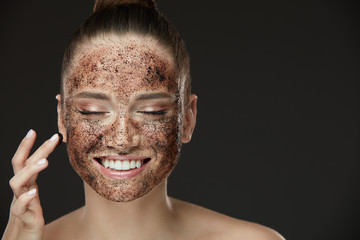 Face Skin Scrub. Smiling Girl Applying Coffee Mask Scrub On Skin