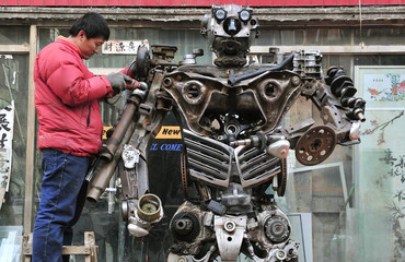 """Huang Lianfei, a worker at a metal craft workshop, stands on a ladder as he drills to construct a model robot based on a character from the cartoon """"Transformers"""", in Shenyang"""