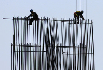 Labourers install steel beams at a new high-rise apartment building under construction in Taguig, Metro Manila