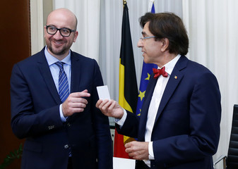 Belgium's new Prime Minister Charles Michel receives the key of the office from outgoing Prime Minister Elio Di Rupo in Brussels
