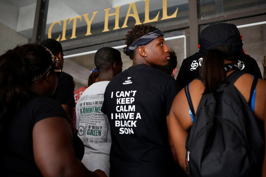 Demonstrators stand in front of the City Hall doors in Baton Rouge, Louisiana