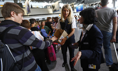 Lufthansa employees give out free beverages to passengers waiting at the check-in counters of Lufthansa at the Fraport airport in Frankfurt