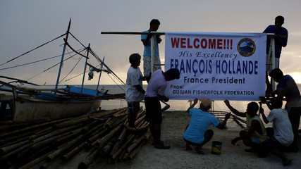 Fishermen install a welcoming banner for French President Francois Hollande, who will visit on Friday, in Guiuan, Samar, that was devastated by Typhoon Haiyan in central Philippines