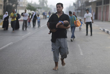 Palestinians flee their houses from Israeli shelling during an Israeli ground offensive east of Khan Younis in the southern Gaza Strip