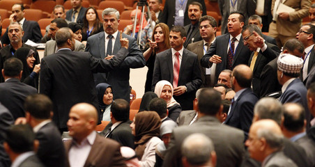 Members of the newly elected Iraqi parliament point fingers at each other after an argument broke out at the parliament headquarters in Baghdad