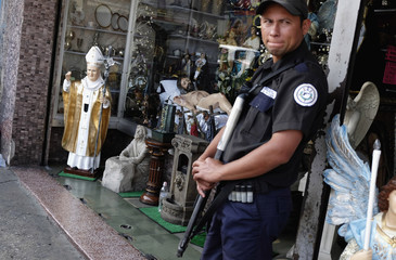A security guard stands near statue of Pope John Paul II at entrance of store selling religious images, downtown before canonisation mass, in Guatemala City
