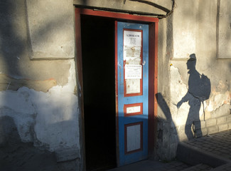 Shadow of man is cast on a wall as he walks along a street in Pustomyty