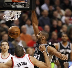 San Antonio Spurs power forward Tim Duncan dunks the ball against Portland Trail Blazers small forward Nicolas Batum during first quarter of their NBA basketball game in Portland