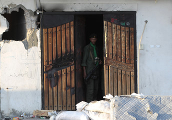 A Libyan soldier loyal to leader Muammar Gaddafi stands near a smashed door of a building in the city of Misrata