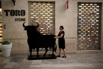 A worker pushes a billboard made in the shape and size of a bull to place it inside a shop in downtown Malaga