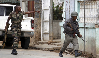 Members of the Madagascar's security force run to take up positions as others storm an army barracks in Ivato