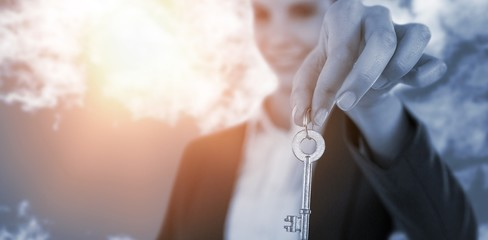 Composite image of smiling businesswoman showing new house key