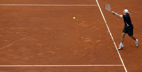 Benjamin Becker of Germany returns the ball to Switzerland's Roger Federer during their Madrid Open tennis match