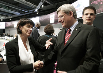 Swiss President Leuthard shakes hands with Canada's Prime Minister Harper after the closing session of the Francophone Summit in Montreux