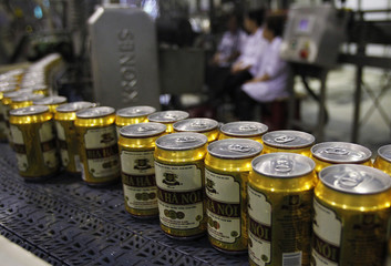 Canned beer move along a production line as factory workers are seen in the background at Hanoi Beer Corporation (Habeco) in Hanoi