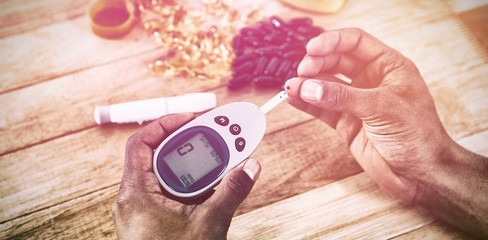 Cropped hands testing blood sugar with glucometer