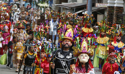"""Penitents called """"Morions"""" parade along the streets of Mogpog town on Marinduque island in central Philippines"""