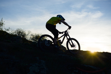Silhouette of Cyclist Riding Down the Mountain Bike on Rocky Hill at Sunset. Extreme Sport Concept.