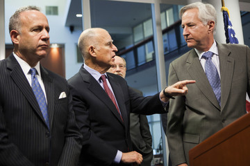 California Governor Brown clarifies an issue with Department of Water Resources Director Cowin during a news conference at the Cal OES State Operations Center in Mather