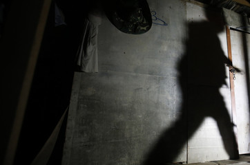 A shadow of a migrant enforcement officer is cast on a makeshift shelter as he tries to break a locked door during a crackdown on illegal migrant workers in Nilai