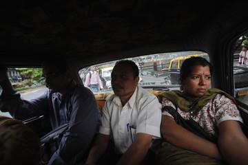 Customers sit in the cramped backseat of Premier Padmini taxi during rush hour in Mumbai