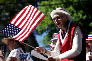 A woman sings while waving an American flag while riding a float through Barnstable Village, on Cape Cod during July 4th parade