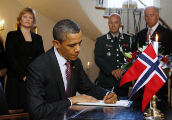 US President Obama signs a book of condolence while visiting the Norwegian Embassy in Washington