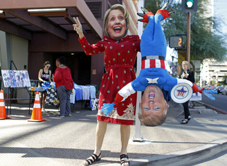 A man wears a mask depicting Democratic U.S. presidential candidate Hillary Clinton while holding a doll depicting Republican presidential nominee Donald Trump in Phoenix