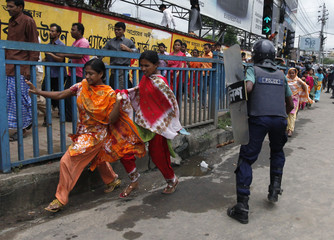 Garment workers run past a police officer during a protest in Dhaka
