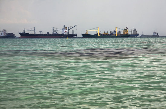 Ships and oil are seen off a beach in Singapore