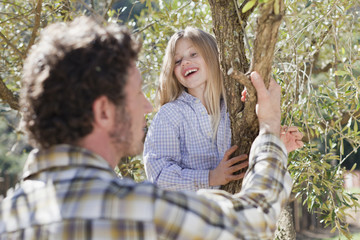 Father and daughter climbing tree