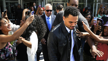 Fans reach out to touch Brown as he leaves the District of Columbia Superior Courthouse in Washington