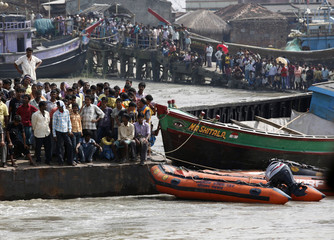 People wait for news of their missing relative on the banks of the Muriganga river after a boat capsized near Ghoramara Island, south of Kolkata