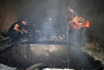 Palestinians inspect the scene where Israeli troops shot dead two Palestinians in the West Bank city of Hebron