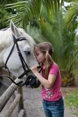 Girl kissing horse in yard