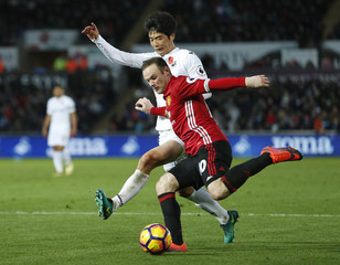 Manchester United's Wayne Rooney in action with Swansea City's Ki Sung Yueng