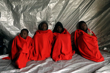 Migrants are covered with thermal blankets following a rescue operation of 104 sub-Saharan migrants aboard an overcrowded raft by the Spanish NGO Proactiva Open Arms, in the central Mediterranean Sea, 24 miles north of the Libyan coastal city of Sabratha