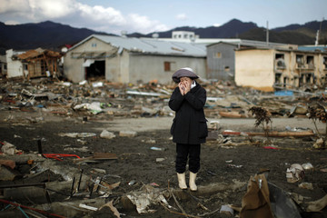 A woman reacts as she looks at her house destroyed by the earthquake and tsunami in Kessenuma town, in Miyagi prefecture